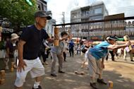 "Japanese pensioners work out in the grounds of a temple in Tokyo on September 17, 2012. Japan's finance minister Taro Aso has said the elderly should be allowed to ""hurry up and die"" instead of costing the government money for end-of-life medical care"