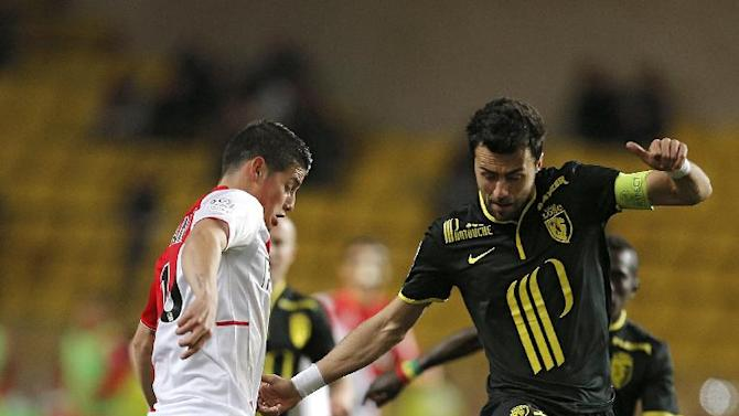 Monaco's James Rodriguez of Colombia, left, challenges for the ball with Lille's Marko Basa of Serbia during their French League One soccer match, in Monaco stadium, Sunday, March 23, 2014