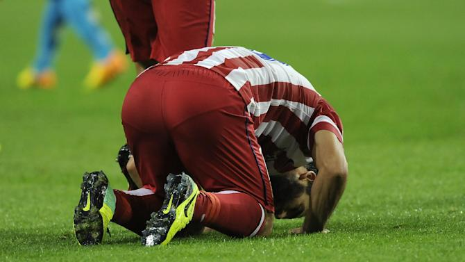 Atletico's Arda Turan kiss the pitch as he celebrates after scoring his side's second goal during the Champions League group G soccer match between FC Porto and Atletico de Madrid Tuesday, Oct. 1, 2013, at the Dragao stadium in Porto, northern Portugal. Atletico won 2-1