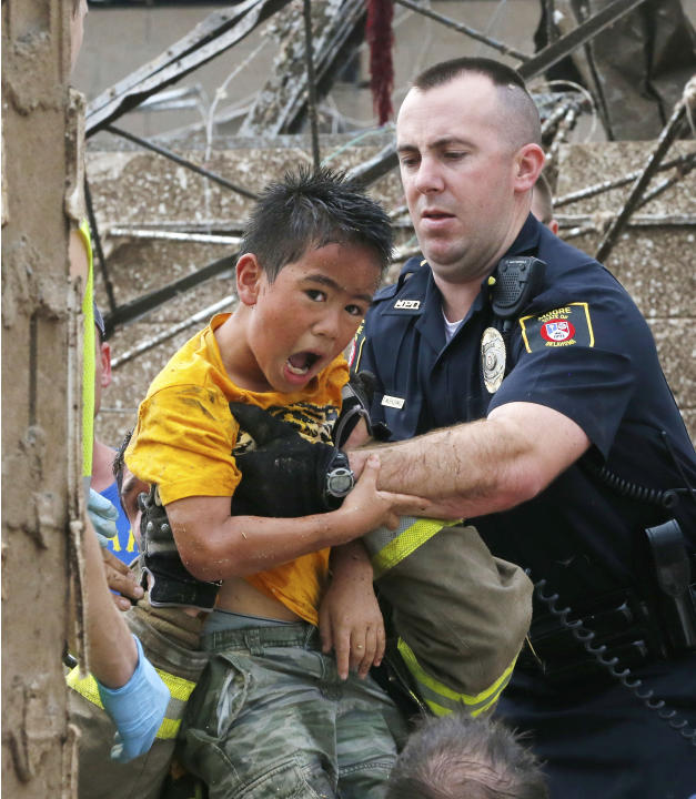 A boy is pulled from beneath a collapsed wall at the Plaza Towers Elementary School following a tornado in Moore, Okla., Monday, May 20, 2013. A tornado as much as a mile (1.6 kilometer) wide with win