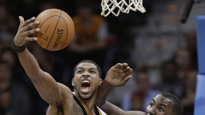 Cleveland Cavaliers' Tristan Thompson, left, from Canada, and Dallas Mavericks' DeJuan Blair battle for a loose ball during the fourth quarter of an NBA basketball game Monday, Jan. 20, 2014, in Cleveland. Dallas defeated the Cavaliers 102-97