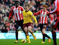 Arsenal midfielder Jack Wilshere (C) holds off Sunderland midfielders Alfred N'Diaye (L) and Jack Colback, at The Stadium of Light, on February 9, 2013. Santi Cazorla fired 10-man Arsenal to a 1-0 away win, but the Gunners' triumph was marred by Wilshere's thigh injury