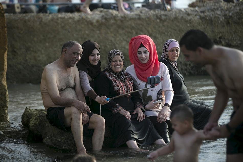 A Palestinian family takes selfie on beach of Mediterranean in Tel Aviv during Eid al-Fitr