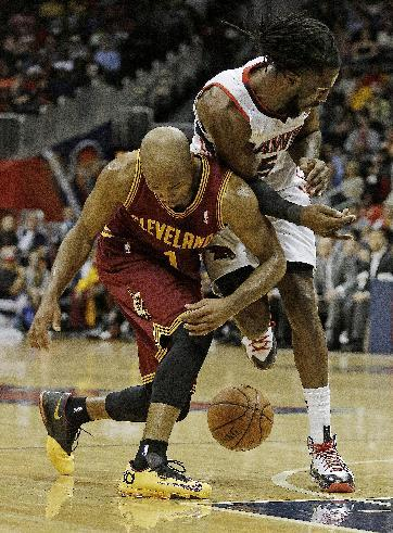 Cleveland Cavaliers point guard Jarrett Jack (1) and Atlanta Hawks small forward DeMarre Carroll (5) collide as they chase a loose ball in the second half of an NBA basketball game Friday, Dec. 6, 2013, in Atlanta