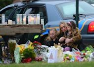 Parishioners pay their respects to the victims of an elementary school shooting while arriving for mass at St Rose of Lima Church in Newtown, Connecticut, on December 16, 2012. In ways big and small, tributes were paid -- from candles lit and teddy bears left at the elementary school crime scene, to gestures at the cavernous football stadiums that usually fixate Americans' attention on Sundays