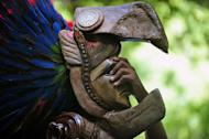 A member of a folk group holds a Maya mask at the Tikal archaeological site on December 20, 2012. The exquisite site of Mayan ruins began hosting winter solstice ceremonies on Thursday as the region's indigenous people marked the end of an era