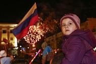 A girl looks back as people watch fireworks during celebrations on the main square of the Crimean city of Simferopol March 21, 2014. REUTERS/Shamil Zhumatov