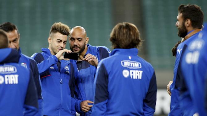 Italy's El Shaarawy and Zaza use mobile phone while standing on the pitch at the Olympic Stadium in Baku