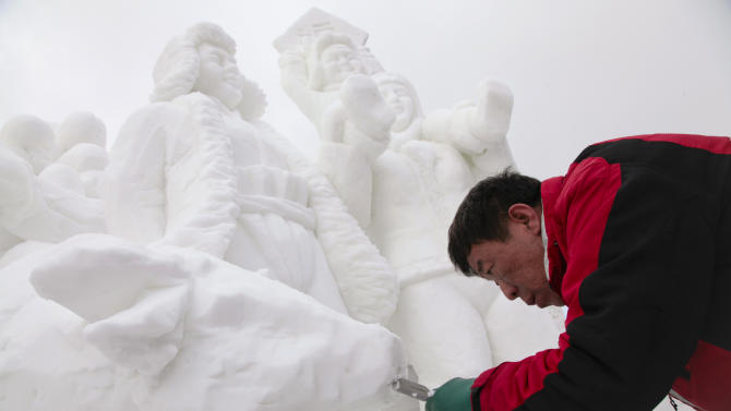 The captain of Team China, Hongchun Liang carving away snow to make the mouth of a cow on his 12 foot tall, 20-ton sculpture at the outdoor art gallery during the 23rd Annual International Snow Sculpture Championships in Breckenridge, Colo., on Friday, Jan. 25, 2013. Liang is joined with 15 international teams, the sculptures will remain on display through Feb. 3, 2013 (weather permitting). Visit www.gobreck.com for more information. (Nathan Bilow / AP Images for The Breckenridge Resort Chamber)