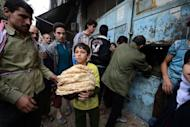A Syrian boy carries a pile of bread as people crowd outside a bakery in the Salaheddin district of the northern city of Aleppo on October 25, 2012. Residents of Aleppo have suffered through months of brutal urban warfare and now face a humanitarian crisis with a lack of food and fuel as the Syrian winter sets in