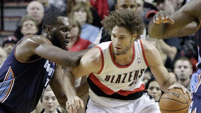 Portland Trails Blazers center Robin Lopez, right, works the ball in against Charlotte Bobcats center Al Jefferson during the first half of an NBA basketball game in Portland, Ore., Thursday, Jan. 2, 2014