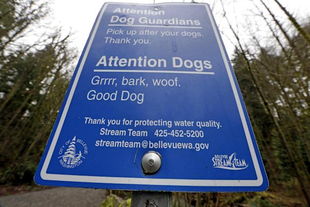 In this photo taken Wednesday, Feb. 11, 2015, a sign posted at an urban watershed trailhead reminds people to pick-up after their dogs to help maintain the health of the nearby salmon-bearing stream i