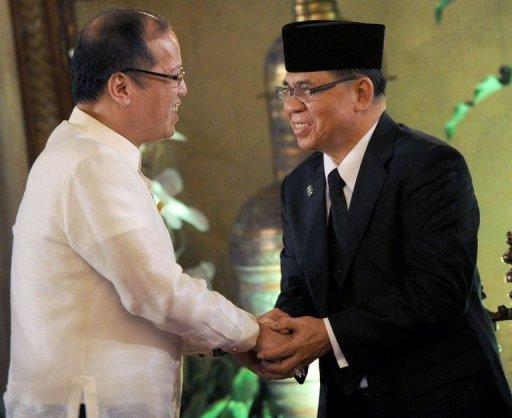 Philippine President Benigno Aquino (left) shakes hands with Moro Islamic Liberation Front (MILF) chief Murad Ebrahim before the signing a framework agreement for peace at a ceremony in Manila. Muslim rebels waging a four-decade insurgency in the Philippines have signed a historic pact with the government to end the conflict, but both sides warned the road to peace had only just begun