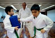 Shigeru Tanida (C) is seen supervising karate students in Kuala Lumpur, on November 3, 2012. Tanida, 65, has lived in Malaysia's capital Kuala Lumpur since 2006, drawn by the year-round sunshine and far lower living costs than in Japan. With its warm climate, political stability and modern economy, Malaysia has drawn 19,488 foreigners to settle in the country during the past 10 years