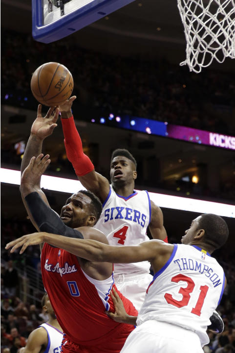Los Angeles Clippers' Glen Davis (0) tries to shoot against Philadelphia 76ers' Nerlens Noel (4) and Hollis Thompson (31) during the first half of an NBA basketball game, Friday, March 27, 201