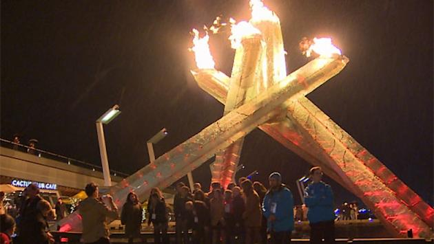 A small crowd applauded and broke into an impromptu rendition of O Canada after Vancouver's Olympic Cauldron was finally lit last night.
