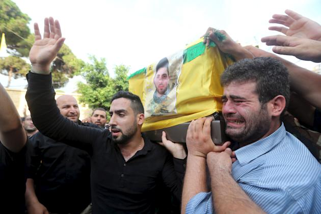Lebanon's Hezbollah members and supporters react as they carry the coffin of Hezbollah fighter Mustapha al-Hooli in Beirut's southern suburbs