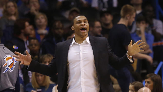 Oklahoma City Thunder guard Russell Westbrook shouts to his teammates from the bench area in the second quarter of an NBA basketball game against the Sacramento Kings in Oklahoma City, Sunday, Jan. 19, 2014. Westbrook is out with an injured knee. (AP Photo/Sue Ogrocki)