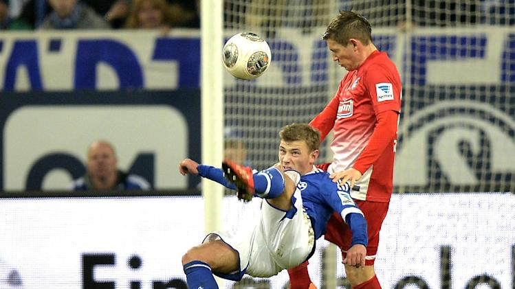 Schalke's Max Meyer, left, performs a bicycle kick  during the German Bundesliga soccer match between FC Schalke 04 and SC Freiburg in Gelsenkirchen, Germany, Sunday, Dec. 15, 2013