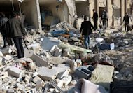 People inspect the scene of an explosion outside Aleppo University on January 15, 2013, in this photo released by the Syrian Arab News Agency. The Britain-based Syrian Observatory for Human Rights said 83 people had been killed in the blasts and at least 150 others wounded, some critically