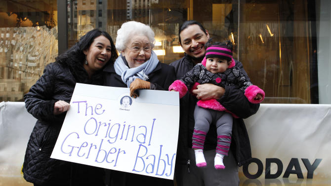 IMAGE DISTRIBUTED FOR GERBER - Mary Jane Montoya, who had the winning photo in the 2012 Gerber Generation Photo Search, poses with her proud parents, Sara and Billy Montoya, and the original Gerber baby, Ann Turner Cook outside Today Show studios after the unveiling of her winning photo on Tuesday, Nov. 6, 2012 in New York City. (Amy Sussman /AP Images for Gerber)