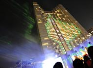 Children look at Christamas illuminations on the Grand Prince Akasaka hotel in Tokyo, on November 6, 2008. Passers-by in Tokyo's busy Akasaka district have started to notice the hotel has shrunk to about half its original height, as the skyscraper is being demolished floor by floor instead of being blown up with explosives or smashed up with a wrecking ball