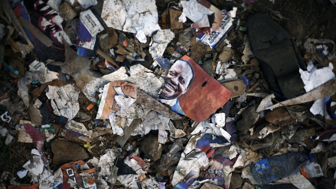 Torn election posters litter the streets of  the Kibera slum of Nairobi, Kenya, Friday, March 8, 2013. Kenyans on Monday held their first presidential vote since the nation's disputed election in 2007 spawned violence that killed more than 1,000 people.  Kenya's last ballots for its presidential race were being counted Friday and Uhuru Kenyatta, the leading candidate, saw his percentage yo-yo above and below the crucial 50 percent mark that would hand him an outright win and avoid a runoff.(AP Photo/Jerome Delay)