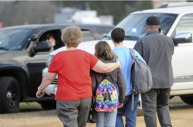 In this Tuesday, Jan. 29, 2013 photo, students and family leave the scene of the school bus shooting. Police, SWAT teams and negotiators were at a rural property where a man was believed to be holed u