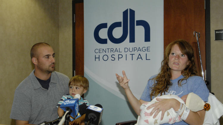 Amber Miller, of Westchester, Ill.,  gestures during a news  conference as she holds her baby at Central DuPage Hospital in Winfield, Ill., Monday Oct. 10, 2011.  Miller felt contractions a few minutes after finishing the Chicago Marathon on Sunday and gave birth hours later to a baby daughter. At left are her husband, Joe, and son, Caleb. (AP Photo/Daily Herald, Mark Black) MANDATORY CREDIT