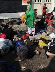 Tarana (R), 11, cries while surrounded by the bodies of men, women and children who died after a suicide bomber detonated a bomb during a religious ceremony in Kabul in 2011