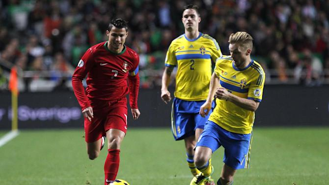 Portugal's Cristiano Ronaldo, left, chases the ball with Sweden's Sebastian Larsson, right, during a World Cup qualifying first leg playoff soccer match between Portugal and Sweden at the Luz stadium in Lisbon, Portugal, Friday, Nov. 15, 2013