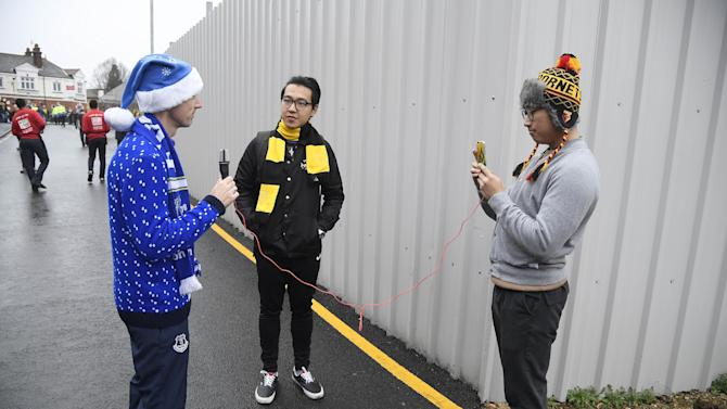 Everton fan who has travelled from Vancouver, Canada, speaks to South Korean media dressed in Watford colours outside the stadium before the match