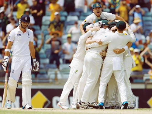 Australia's players celebrate winning the Ashes Test cricket series against England as England's James Anderson (L) reacts at the WACA ground in Perth Tuesday. — Reuters