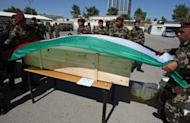 Palestinian security forces cover a coffin with the national flag ahead of the funeral procession of 91 Palestinians whose remains were returned by Israel in the West Bank city of Ramallah on Thursday