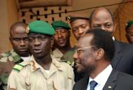 Mali's interim president Dioncounda Traore (R, with glasses) stands next to coup leader Captain Amadou Sanogo (2nd L) after a meeting April 9, at the Kati military barracks outside Bamako. Armed men rounded up top Malian officials including two presidential hopefuls, in a show of force by the junta that seized power last month, as the interim leader named a Microsoft executive as prime minister