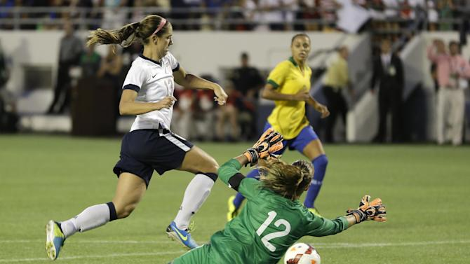 Brazil goalkeeper Luciana (12) guards against a shot by U.S. forward Alex Morgan (13) during the second half of an international friendly soccer match in Orlando, Fla., Sunday, Nov. 10, 2013. United States Women's national team defeated Brazil 4-1