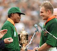 Nelson Mandela congratulates South Africa's rugby captain Francois Pienaar before handing him the Webb Ellis Cup in Johannesburg on June 24, 1995