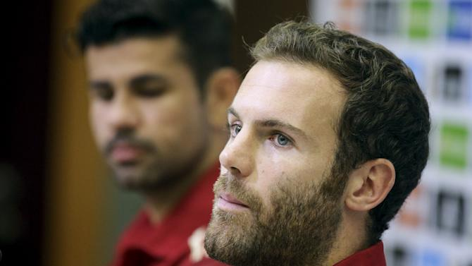 Spain players Juan Mata and Diego Costa listen to a question at the beginning of a news conference at Soccer City grounds in Las Rozas, near Madrid, Spain