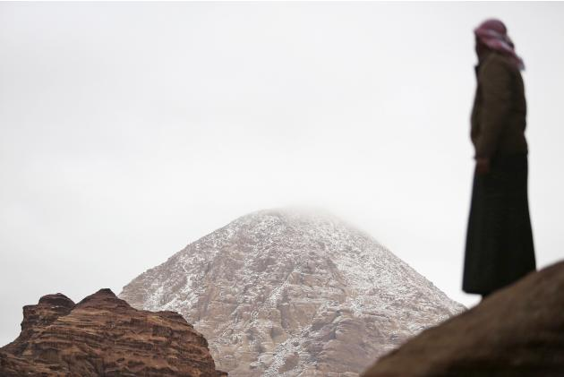 A Saudi man stands during a snowfall in the desert near Tabuk