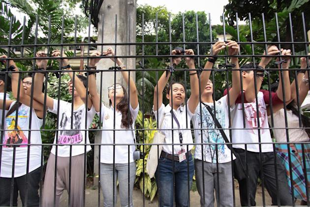 Students tie black ribbons in front of University of the Philippines campus in Manila on 18 March 2013. The students demand justice for the death of Kristel Tejada, a freshman student at UP Manila, who committed suicide for after reportedly being forced to go on leave because her family could not afford to pay tuition. (Czeasar Dancel/NPPA Images)