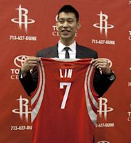 Jeremy Lin of the Houston Rockets displays his jersey during a press conference at Toyota Center, on July 19, in Houston, Texas