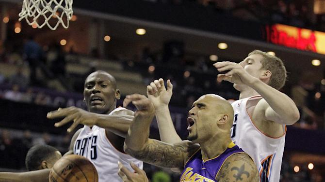 Los Angeles Lakers' Robert Sacre, center, loses the ball under the basket as the Charlotte Bobcats' Bismack Biyombo, left and Cody Zeller, right, battle during the first half of an NBA basketball game in Charlotte, N.C., Saturday, Dec. 14, 2013