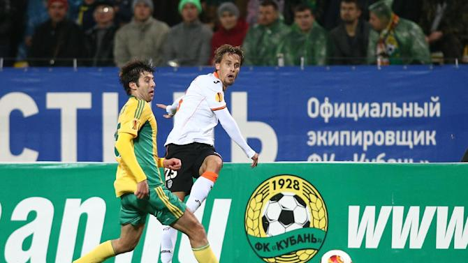 Kuban's ngel Dealbert, left, tries to block the ball from Valencia's Sergio Canales during their Europa League Group A soccer match in Krasnodar, Russia, Thursday, Oct. 3, 2013
