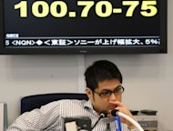 "A money dealer works before an exchange rate board quoting 100.50-55 yen against the euro at a Tokyo foreign exchange market on June 18, 2012. Japan welcomed the result but called on Europe to ""urgently"" strengthen its financial sector and pressed Greece to swiftly form a new government"
