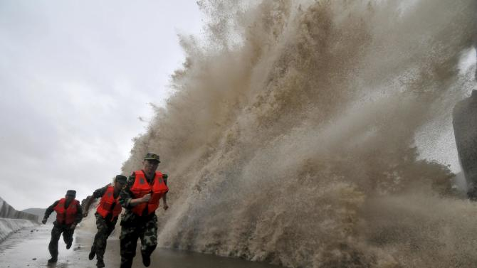 Frontier soldiers run as a storm surge hits the coastline under the influence of Typhoon Fitow in Wenling, Zhejiang province