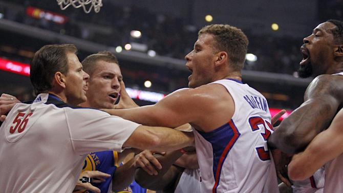 Referee Mark Ayotte, left, breaks up a scuffle between Los Angeles Clippers center DeAndre Jordan, right, and Golden State Warriors Andrew Bogut (not shown) with  Clippers forward Blake Griffin, center, trying to keep the peace with Warriors forward David Lee, second from left, in the second quarter during an NBA basketball game on Thursday, Oct. 31, 2013, in Los Angeles