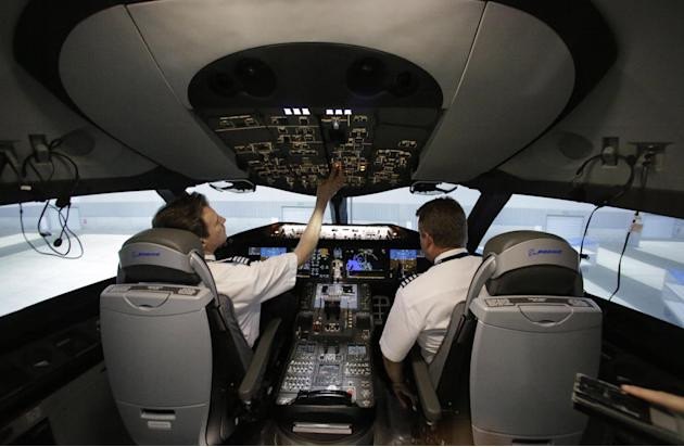 ADVANCE FOR US MONDAY, MARCH 9, FILE - In this May 9, 2014, file photo, American Airlines pilots Bill Elder, left, and Jim Dees work inside a Boeing 787 flight simulator with New York's JFK airport ga