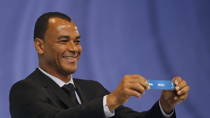 """Cafu holds the slip showing """"Brazil' during the draw for the 2014 World Cup in Sao Joao da Mata"""