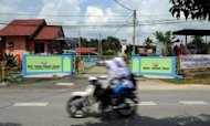 Malaysian students ride past the main enterence of the Lenggeng immigration depot in the south of Kuala Lumpur in April. Malaysia is to offer amnesty to some of its two million illegal immigrants in a plan to ease labour shortages in the plantation and service industries, a senior minister said Monday