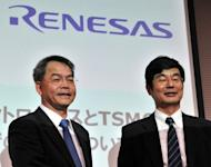 Senior vice president for Japan's chipmaker Renesas Electronics, Shinichi Iwamoto (R), shakes hands with specialty technology director for the world's largest chip maker, Taiwan Semiconductor Manufacturing Company (TMSC), Lin Cheng-Ming, at a press conference in Tokyo. Renesas Electronics said it will boost the outsourcing of its chip production to Taiwan's TSMC